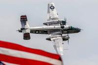 "B-25 Mitchell ""Panchito"" flies past the Stars and Stripes during its demonstration at the Joint Base Andrews Air Show."