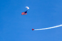 Circled by Clemens Kuhlig in his Pitts Special, a member of the USAF Academy's Wings of Blue Parachute Team brings in the flag to open the Thunder Over Dover Airshow.